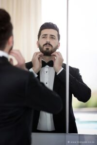 Groom getting ready, putting on bowtie looking dapper groom.