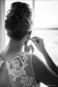 Bride getting ready, putting on earrings. Back of wedding dress details