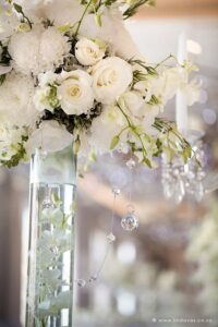 Luxury White wedding reception, flower balls. These white flower spheres are white with orchids, roses and crystal details like crystal garlands