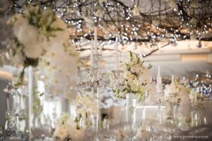 Luxury white wedding reception with lush white flowers on stands, crystal candelabra, crystal garlands, hanging roof installations of branches, fairy lights and white flowers