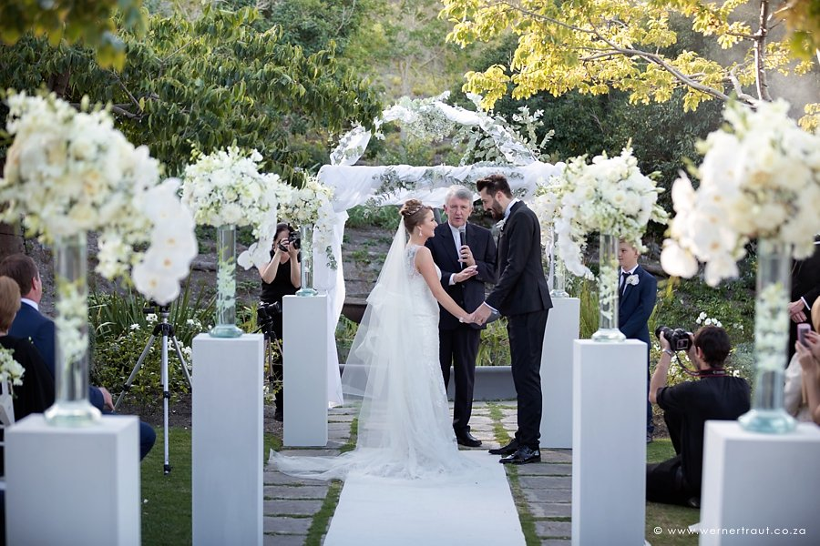 Saying their I do's at the altar. Luxury white wedding ceremony setup with lush white orchids on white plinths and white carpet
