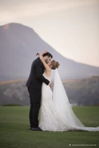 Bride and groom kissing with scenic views of mountains on beautiful green grass