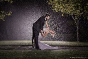 Bride and groom dancing in the rain night shot