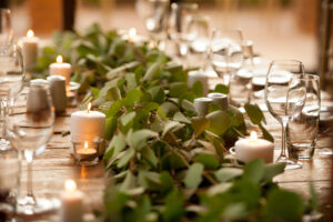Guests tables, greenery runner, candles on wooden tables. Romantic wedding table setup