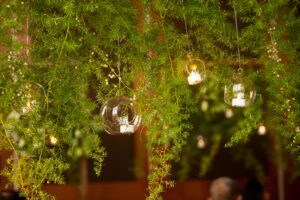 Hanging centrepieces for guests tables. Greenery leaves and glass balls with t-light candles