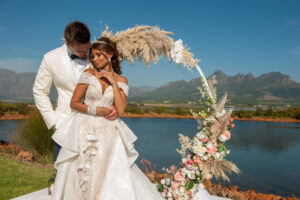 Bride and groom, ceremony arch, pampas grass, mountain views